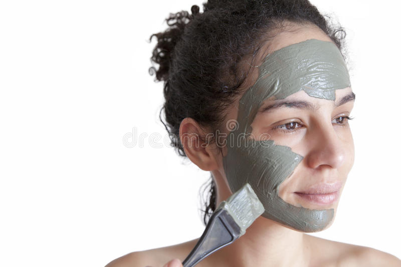 Green clay facial mask in beauty spa. Beautiful young Brazilian woman with green clay facial mask royalty free stock image