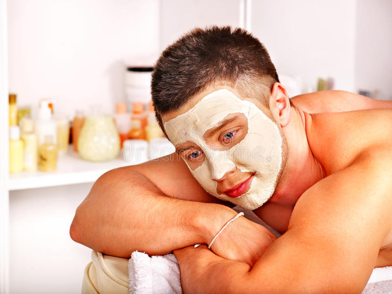 Clay facial mask in beauty spa. Man with clay facial mask in beauty spa stock photos