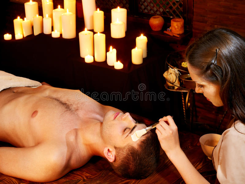 Clay facial mask in beauty spa. Man with clay facial mask in beauty spa stock photo