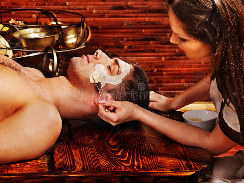 Clay facial mask in beauty spa. Man with clay facial mask in beauty spa royalty free stock photos