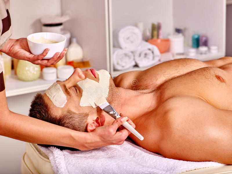 Clay facial mask in beauty spa. Man with clay facial mask in beauty spa. Make up brush stock image