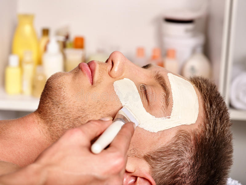 Clay facial mask in beauty spa. Man with clay facial mask in beauty spa. Male face close up royalty free stock photos
