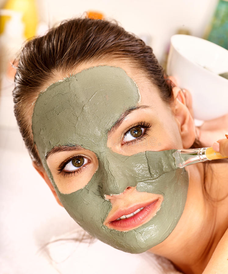 Clay facial mask in beauty spa. Woman with clay facial mask in beauty spa stock images