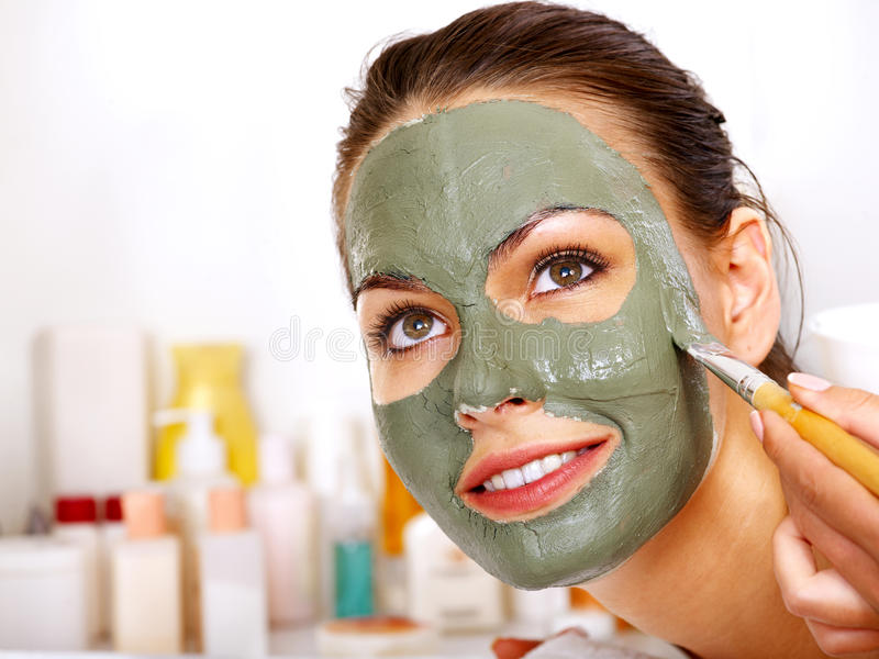 Clay facial mask in beauty spa. Woman with clay facial mask in beauty spa royalty free stock photo