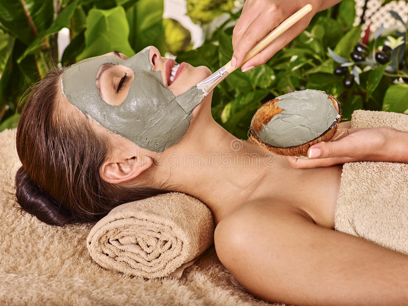 Clay facial mask in beauty spa. Woman with clay facial mask in beauty spa. In background tropical plants royalty free stock photo