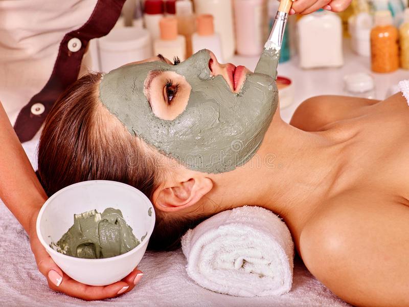 Clay facial mask in beauty spa. Woman with green clay facial mask in beauty spa stock photos