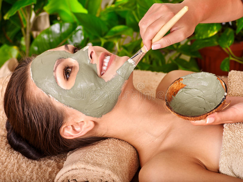 Clay facial mask in beauty spa. Woman with clay facial mask in beauty spa. Towel under the neck stock photos