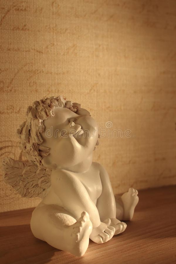 Statuette of angel boy with blessing smile sitting on shelf in sunshine. stock photography