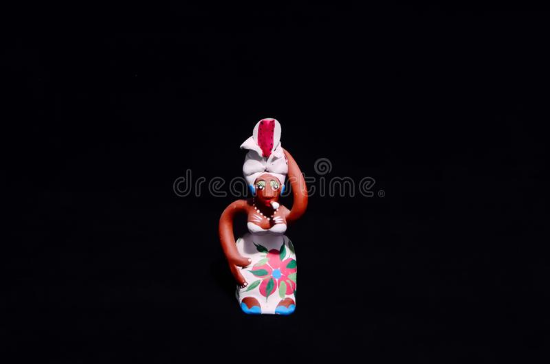 Clay Handmade Statuette of a Cuban Woman. Clay Handmade Statue of a Cuban Woman on Black Background stock photography