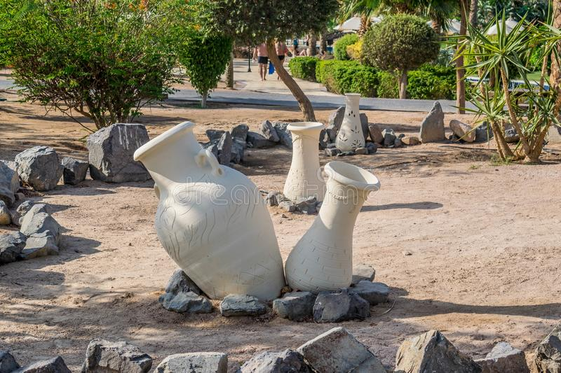 Clay jugs. Decoration on the sand. Earthenware jugs. Decoration on the sand. Paths, palm trees and well-groomed trimmed shrubs. Territory of the Steigenberger Al stock photography