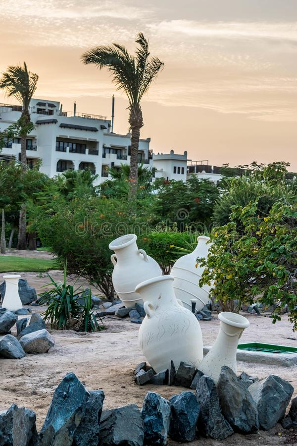 Clay jugs. Decoration on the sand. Territory of the Steigenberger Al Dau Beach Hotel in Hurghada, Egypt. The sky is filled with yellow sunset light stock photos