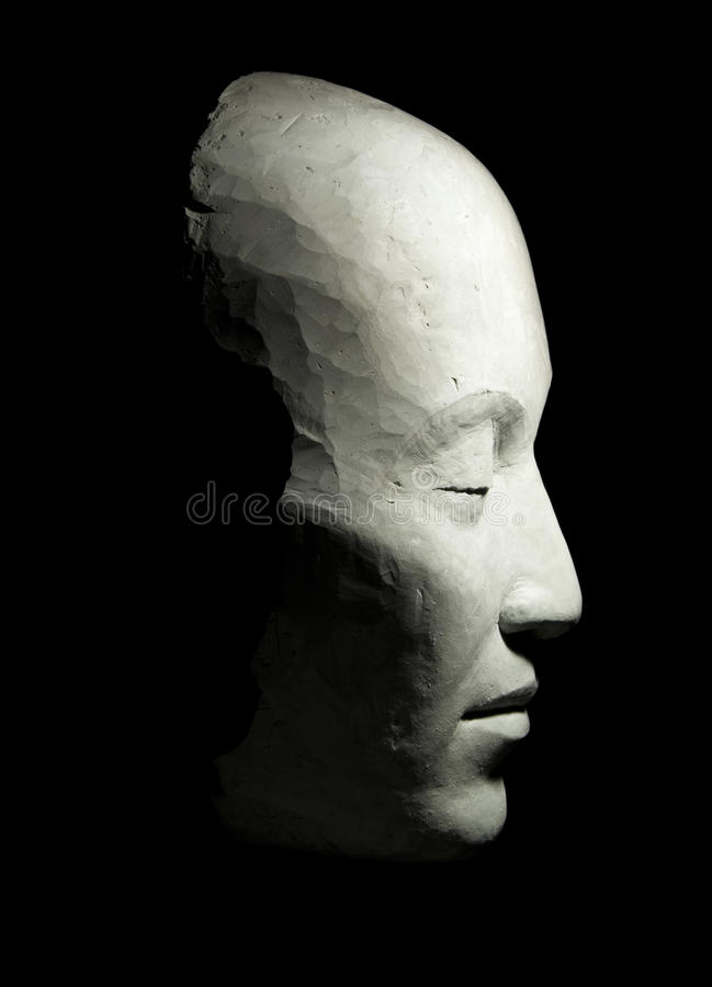 Clay mask. Human face mask, in profile, blindly, east type, executed from clay against a dark background stock photos