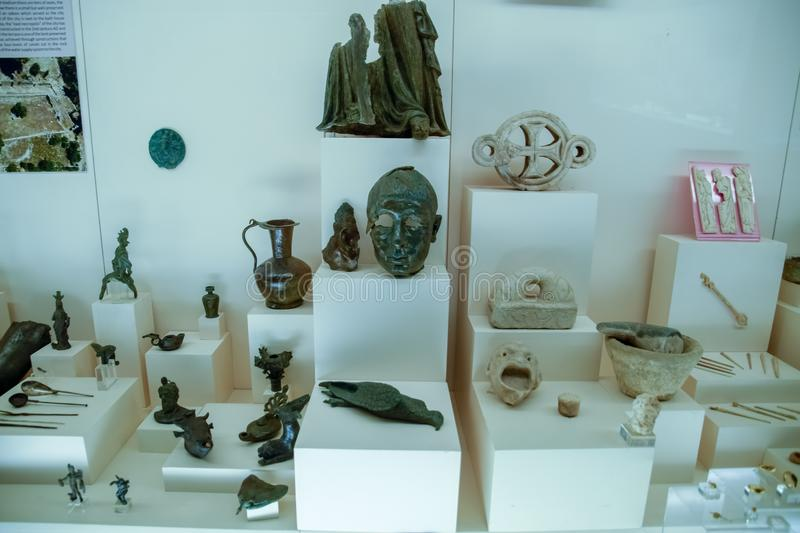 Clay and metal dishes and clay figurines and figurines in the museum of antiquity of Antalya. Antalya, Turkey - May 20, 2019: Clay and metal dishes and clay stock photos