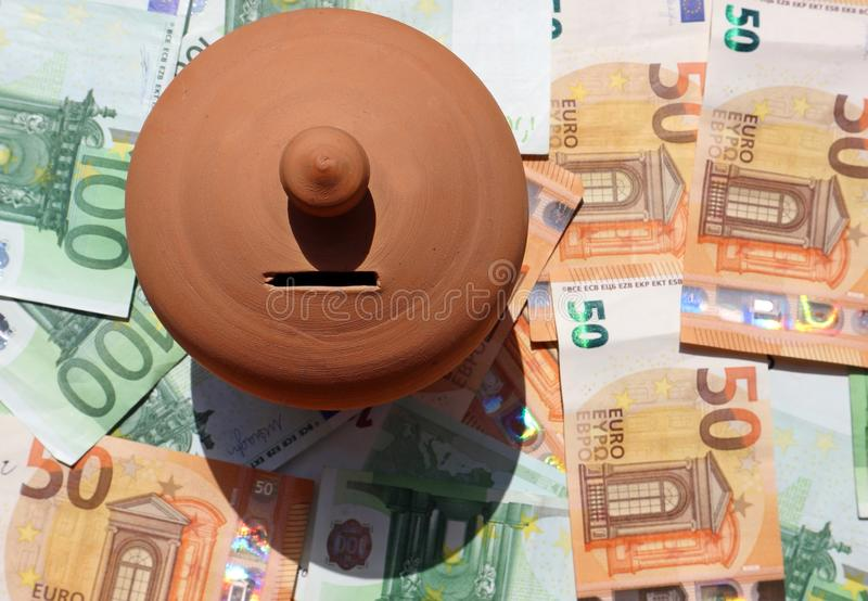 Clay money saving box, or piggy bank, on a bed of euro banknotes scattered stock photography