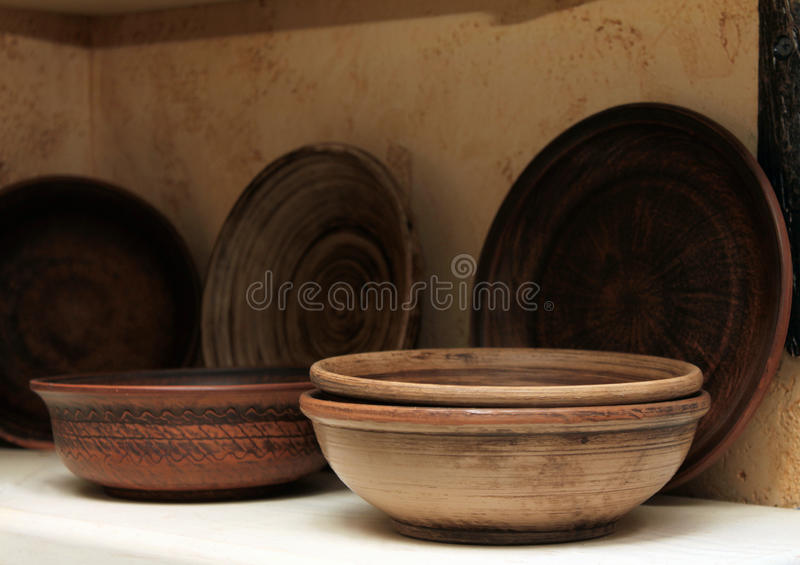 Clay plates on a shelf close-up. Clay plates on a shelf close up royalty free stock images