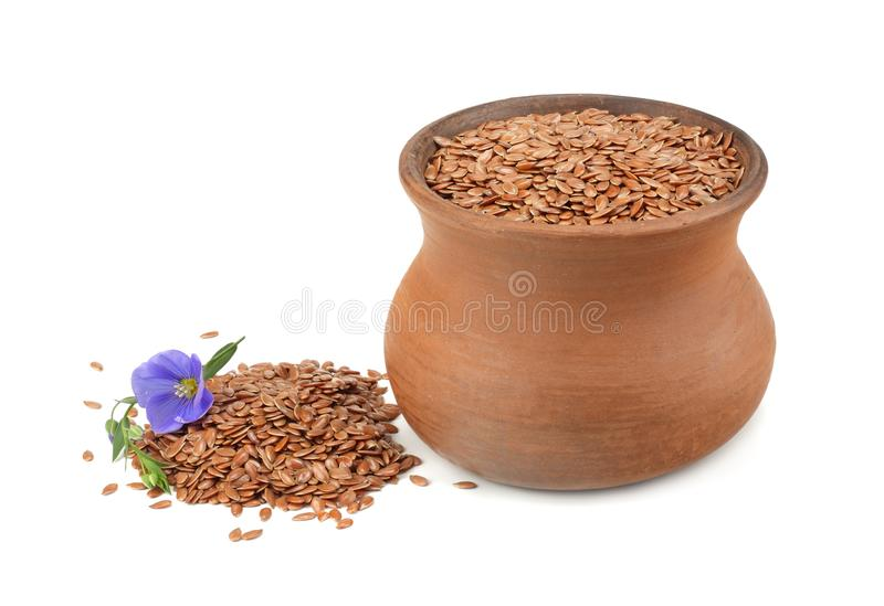 Clay pot with flax seeds and flower isolated on white background. flaxseed or linseed. Cereals. royalty free stock photo