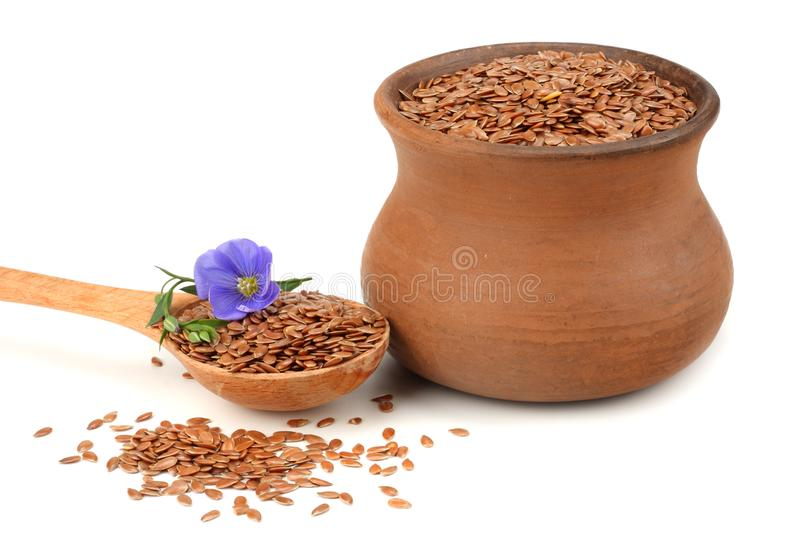 Clay pot with flax seeds and flower isolated on white background. flaxseed or linseed. Cereals. royalty free stock image