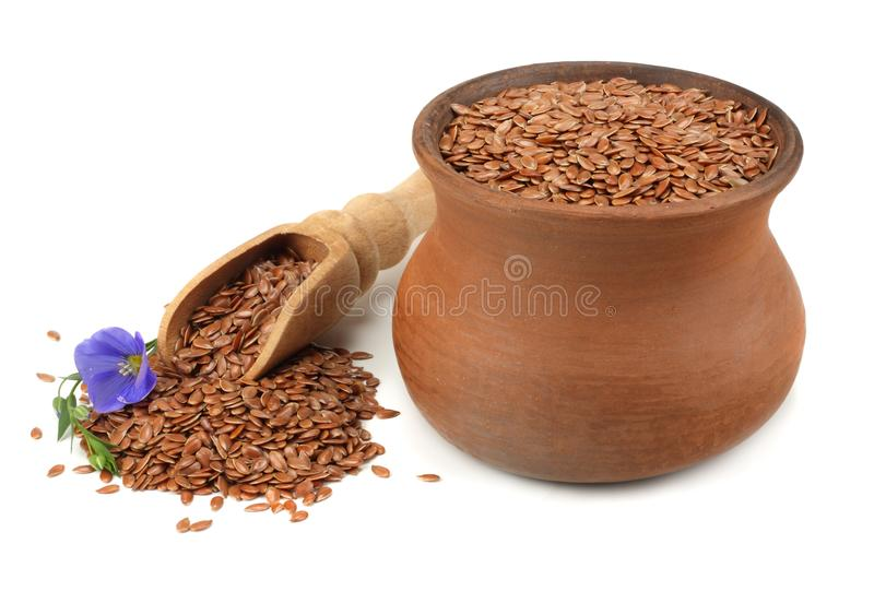 Clay pot with flax seeds and flower isolated on white background. flaxseed or linseed. Cereals. royalty free stock photography