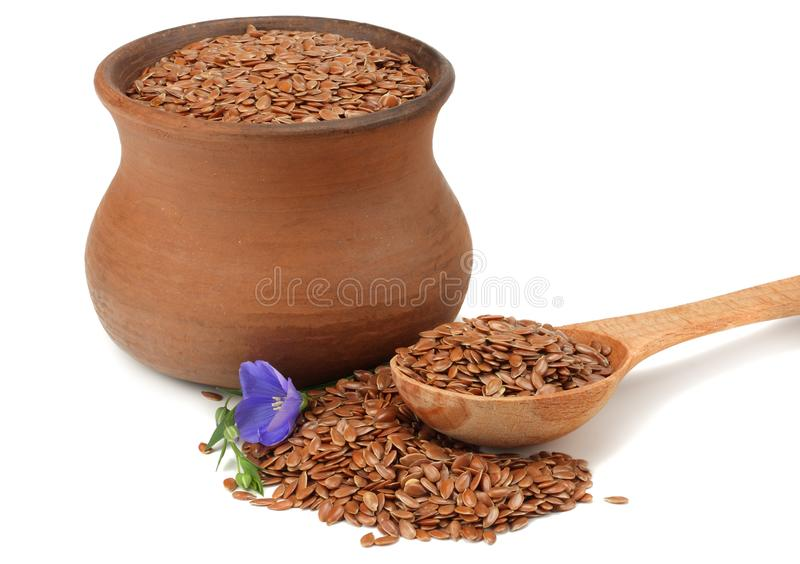 Clay pot with flax seeds and flower isolated on white background. flaxseed or linseed. Cereals. stock images
