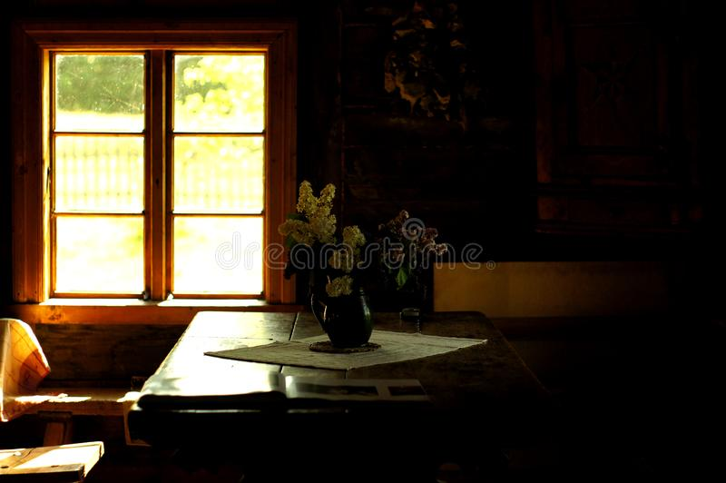 Clay pot and flower bouquet at the table near the window. Riga city nearby, Latvia. Vintage retro still life photo royalty free stock images