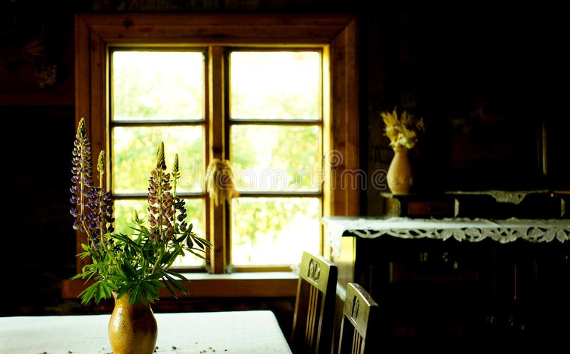 Clay pot and flower bouquet at the table near the window. Vintage retro still life photo. Village house interior concept stock photo