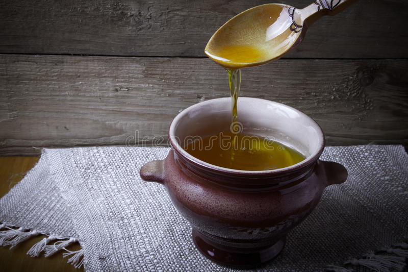 Clay pot with ghee and spoon on linen napkin. Rustic still life. stock image