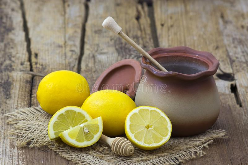 Clay pot with honey and fresh lemons. On wooden background stock photos