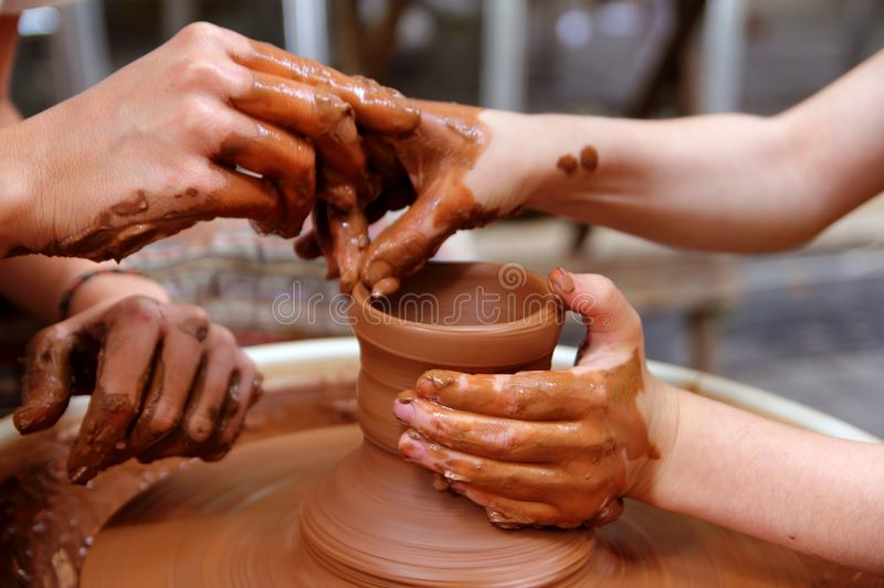 Clay potter hands wheel pottery work. Workshop teacher and pupil royalty free stock photography