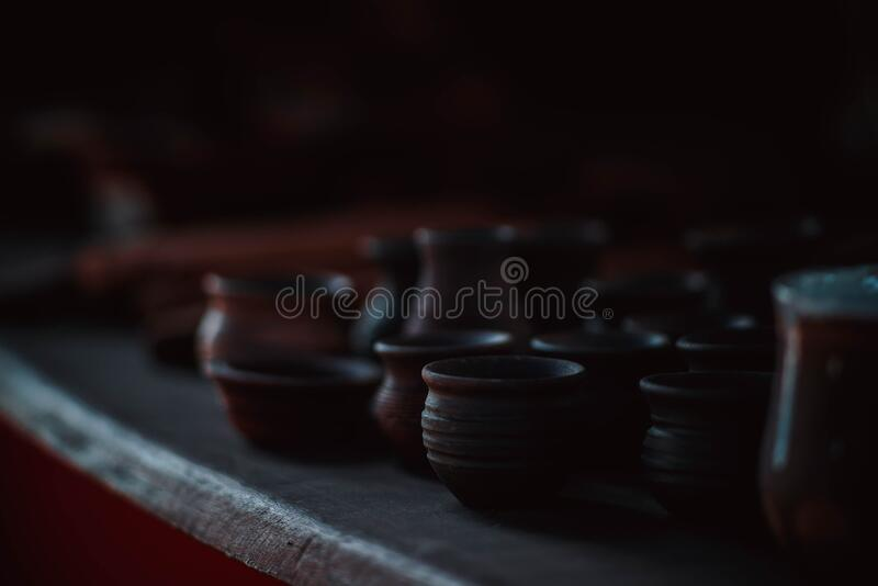 Clay products, cups, bowls, glasses stand on a wooden shelf stock images