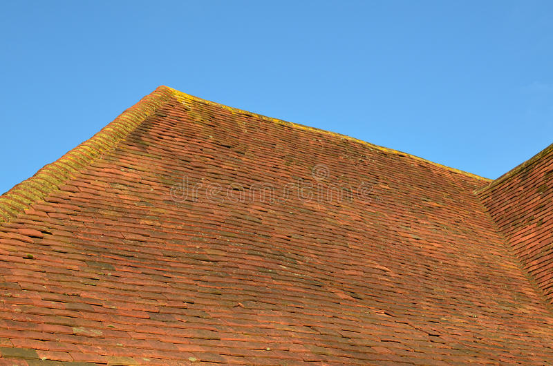 Clay ridge and roof tiles. An English pre 20th century building with traditional clay roof tiles stock image