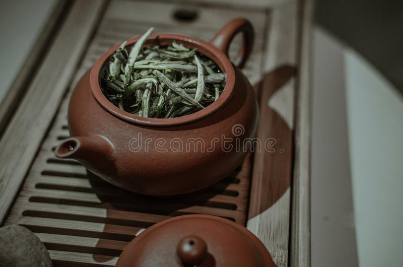 Clay tea pot with portion of white tea on a wooden table close-up royalty free stock photos