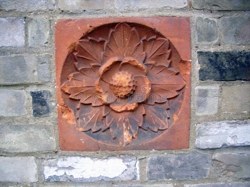 Clay tile with flower motif in brick wall stock image
