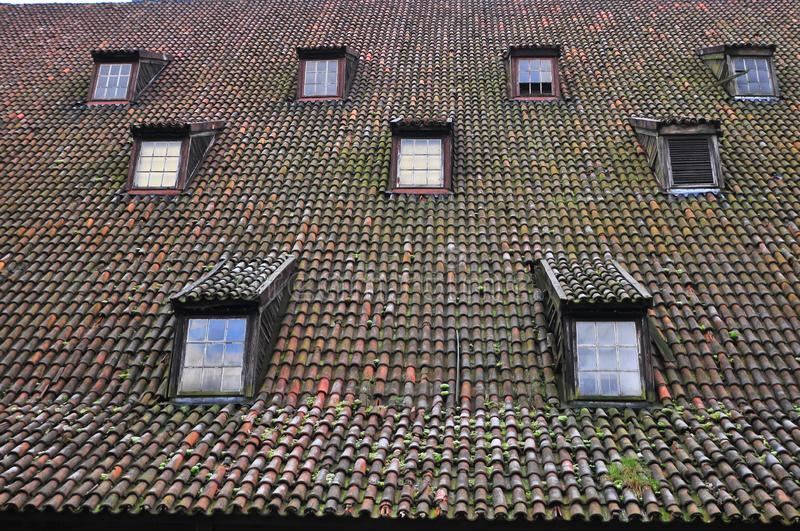Clay tiles roof and windows on a very old building. Clay tiles roof and windows on a very old building stock photography