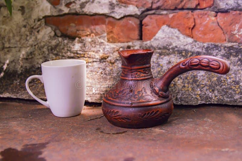 Clay Turk para o café e um copo branco em um fundo da parede de tijolo foto de stock