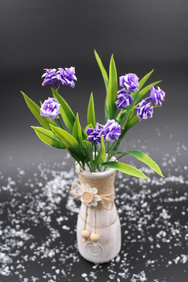 Clay vase with purple flowers royalty free stock images
