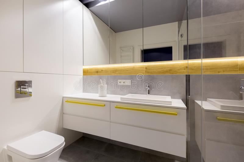 Clean bathroom with gray tiles. Clean, modern bathroom interior with a toilet, white cabinets, yellow handles, mirrors and gray tiles stock photography