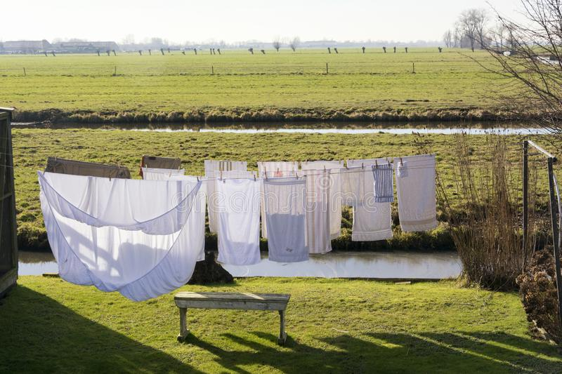 Clean clothes drying in the wind on a washing line on a beautiful sunny day in spring. Situated in a beautiful typical Dutch flat landscape with grassland royalty free stock photo