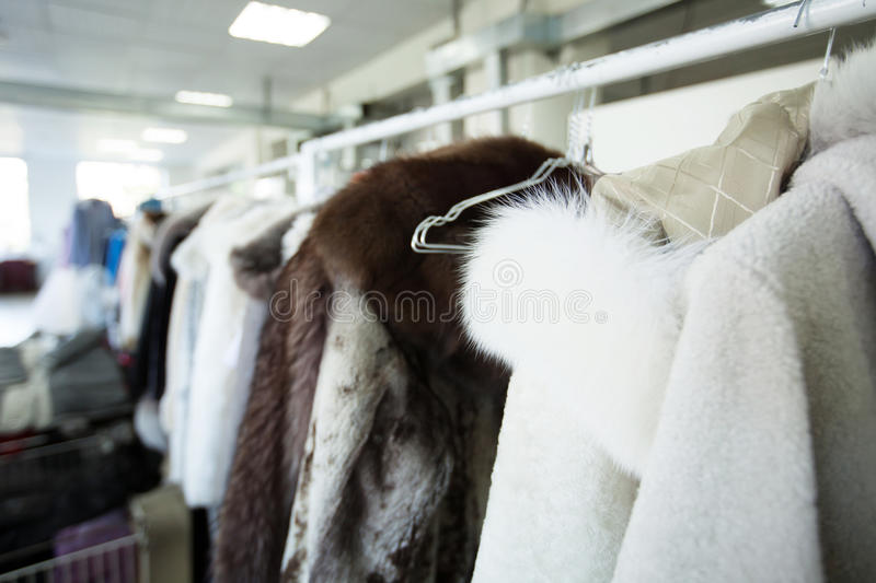 Clean clothes hanging on hangers at dry cleaner's. Close-up stock photography