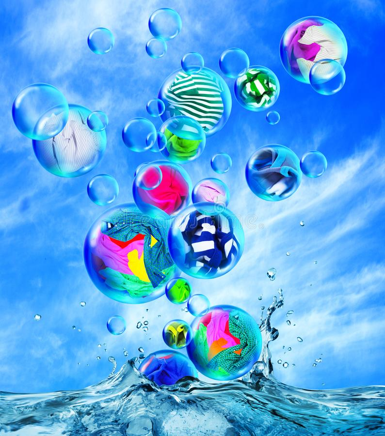 Clean clothes are in soap bubbles fly out of the water. Against the background of a cloudy sky stock image