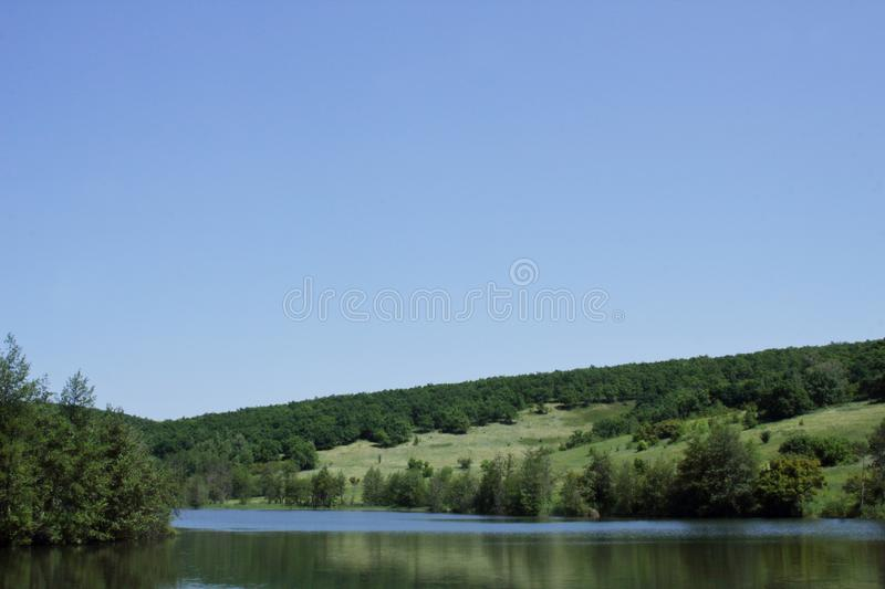 Clean cold spring lake among hills covered with forests in Russian remote place on a summer day. Outdoor. Tourist routes of Russia. Beautiful clean spring lake royalty free stock photos