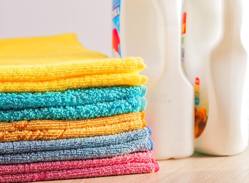 Clean, colorful, folded clothes. Means for washing clothes. Clothes after washing. Aroma of clean linen. White bottles with detergent stock photos