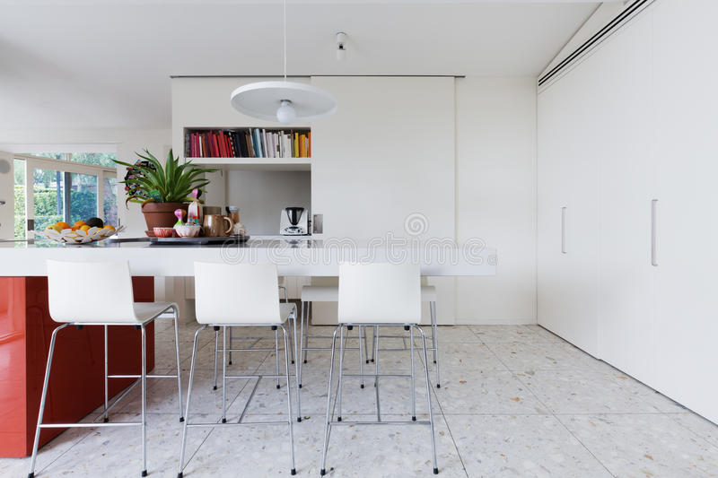 Clean crisp white modern kitchen island bench with high chairs stock photo