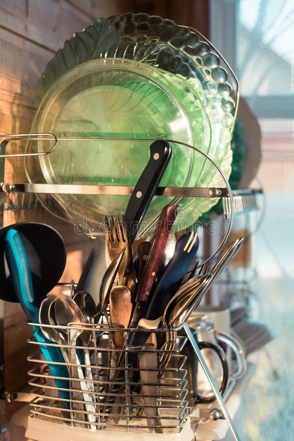 Clean cutlery in the dishwasher. Home equipment. Work at home concept. Home kitchen. Clean washed dish ware drying on a drainer mounted in kitchen. Clean dishes stock images