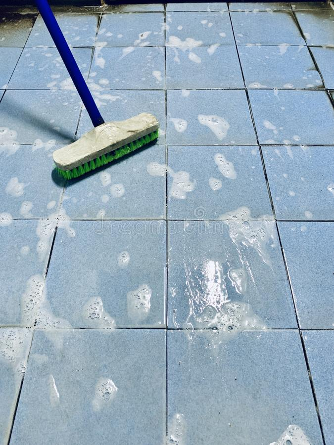 Clean the dirty floor with a scrub brush. royalty free stock photography