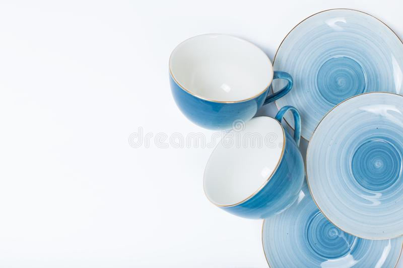 Clean dishes, coffee or tea set. Plenty of elegant porcelain cups and saucers at white royalty free stock photography