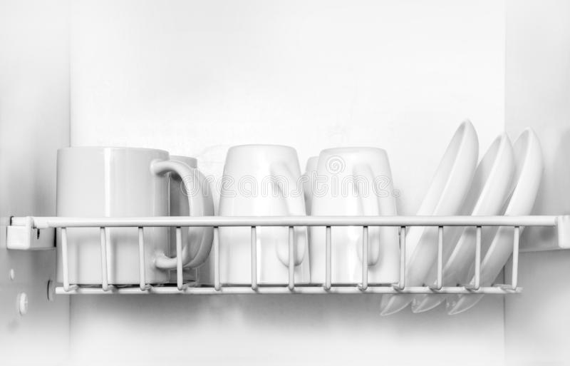 Clean dishes drying on metal dish rack stock photography