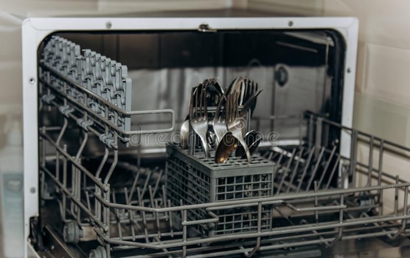 Clean dry forks and spoons in an open dishwasher closeup. cutlery compartment close-up. household appliances in the kitchen stock photography