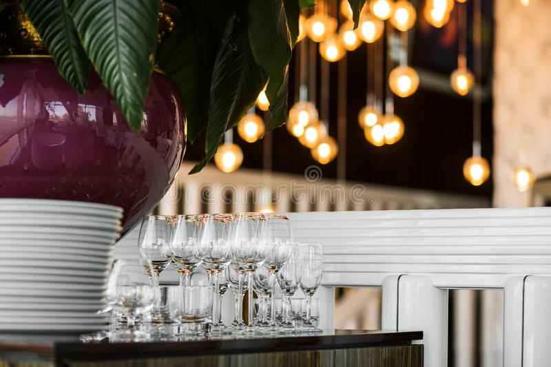 Clean empty glasses stand on the table next to a stack of white plates with a white tablecloth in a restaurant indoors. Buffet at. The party. Garlands of lights stock images