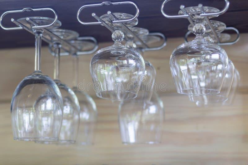 Clean empty wine glasses, cognac glasses in row hang on shelf bar in light sunshine stock image