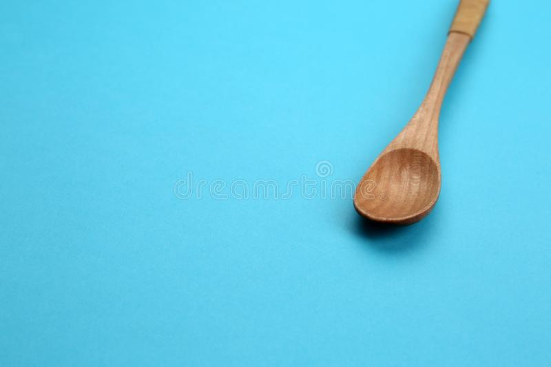 Clean empty wooden spoon on blue background. Space for text stock image